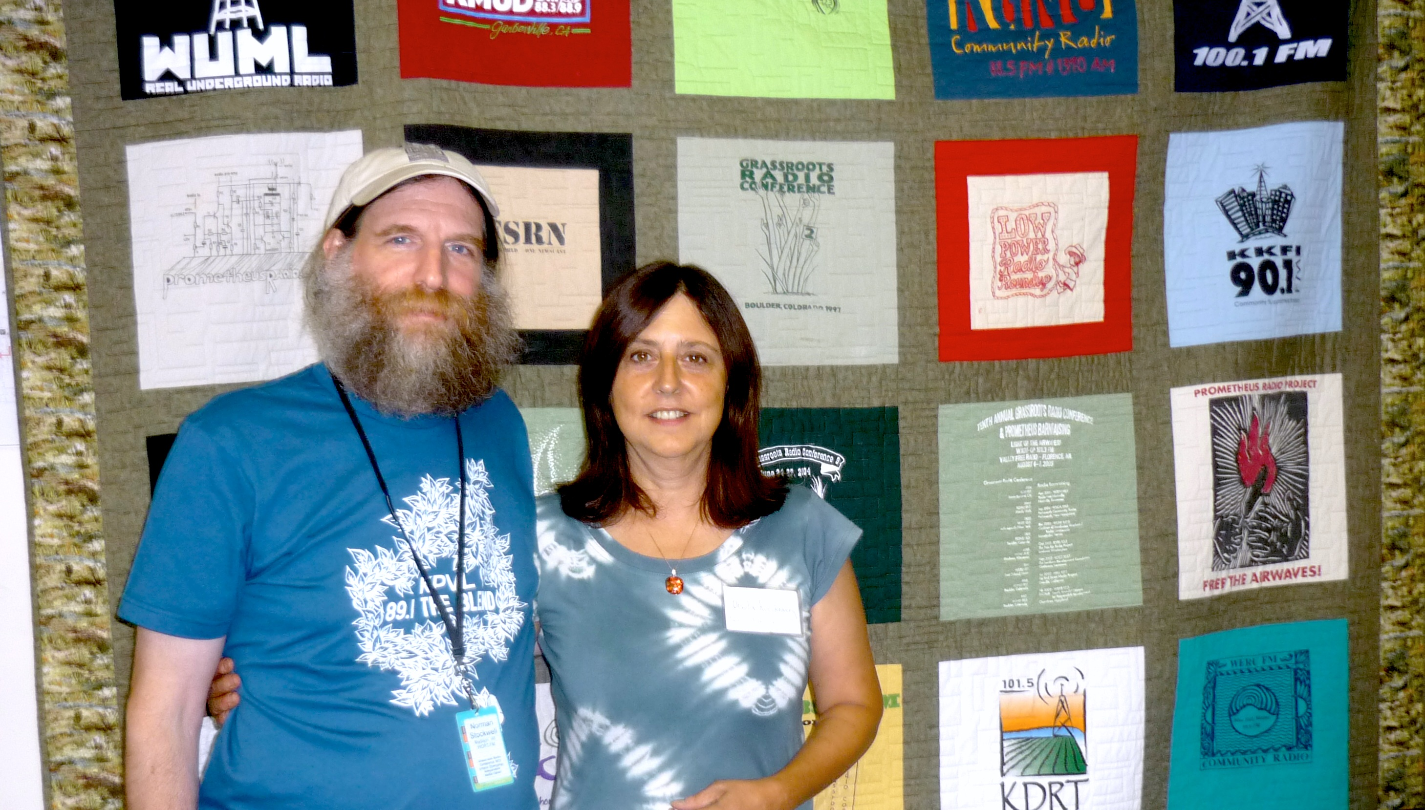 June 27, Urbana, Illinois – Norman Stockwell, WORT (Madison, WI) Operations Coordinator with Pacifica Affiliates Coordinator Ursula Ruedenberg, in front of the GRC Community Radio Quilt. Stockwell had just received Pacifica Network's Annual GRC Outstanding Service to Community Radio at the Pacifica Affiliates Meeting during GRC Conference.